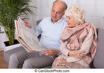 Time to read whats happening in the world - Elderly couple...