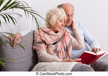 The story of our love. - Elderly marrried couple reading a...