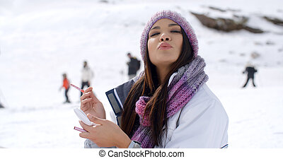 Young woman blowing a kiss at the camera as she stands...