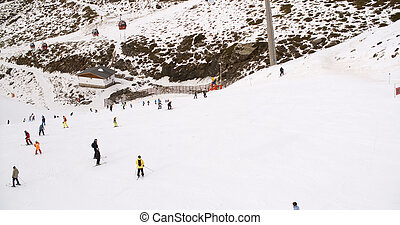View from a ski lift of skiers below on run - View from a...