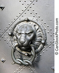 Old door with lion head - A bronze knocker in the shape of a...
