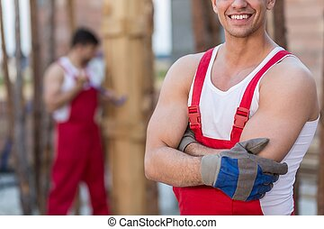 Builders in red work dungarees - Picture of two builders in...