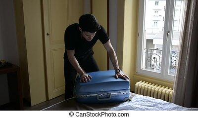 Young man trying to close his suitcase