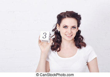 Girl in white t-shirt holding number three.