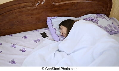 sleeping woman in bed - Woman awakened by the phone ringing