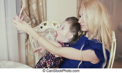 Mother and daughter are doing selfie