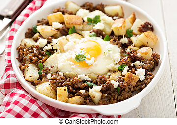 Potato hash with sausage and fried egg in a baking dish