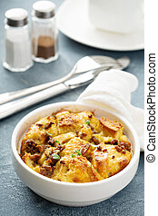 Breakfast strata with cheese and sausage in small baking...