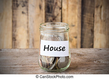 Coins in glass money jar with house label, financial...