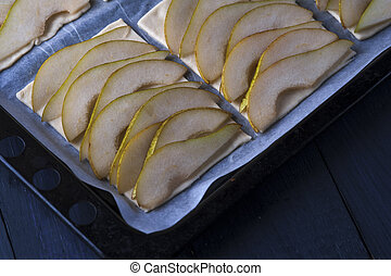 Puff pastry with pear slices on baking pan