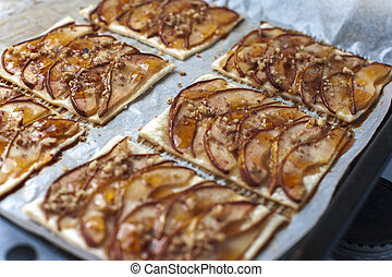 Tarte with puff pastry, pears, walnuts on baking pan