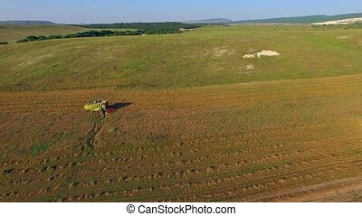 AERIAL VIEW. Farm Machinery Cutting Field At Harvest