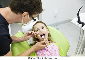 Girl sitting on dental chair on her regular dental checkup -...