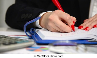 Businesswoman writing in diary. Close up