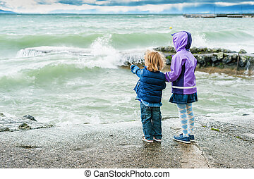 Adorable children playing next to lake on a stormy day, back...