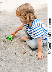 Toddler boy playing in the sandbox