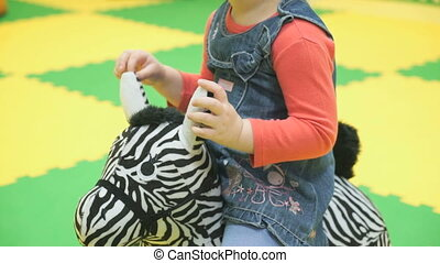Child is ridden on a toy zebra at a nursery school