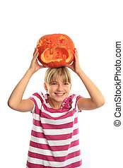Girl and halloween - Smiling girl puts a halloween pumpkin...