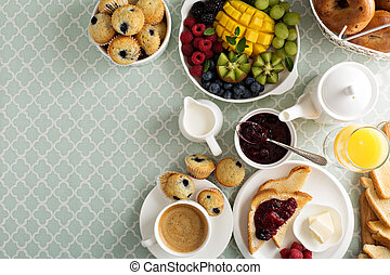 Fresh and bright continental breakfast table with fruit...