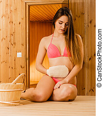 Woman in sauna with exfoliating glove. Skincare.