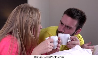 Young happy amorous couple with coffee or tea drink at home,...
