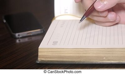 Man hand going write something in notebook by a pen, but phone ring. Close up
