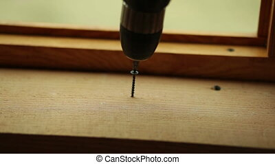 screwdriver screw twists into the board