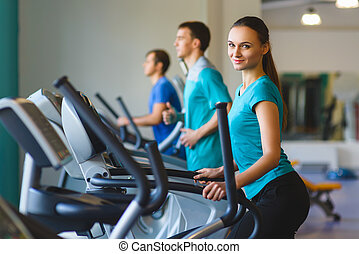 Woman exercising at the gym on a cross trainer