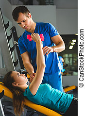 Young womanexercising with dumbbells in a gym