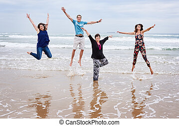 Happy family jumping together on the beach in landscape -...