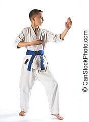 Karate boy in kimono fighting on a white background