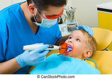 Dentist treats teeth of patient in dental clinic