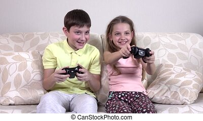 Little brother and sister playing video games lying on the...