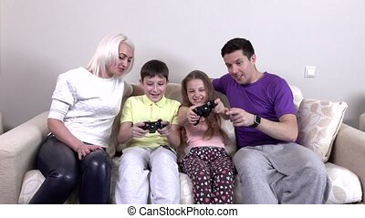 Family playing video games in the living room, beautiful...
