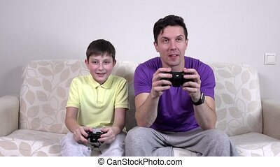 Father and son playing video games, claps, happy childhood,...