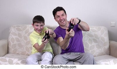 Man and young boy with video game controllers smiling, happy...