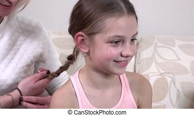 Mom makes daughter hairstyle, girl sitting on the couch,...