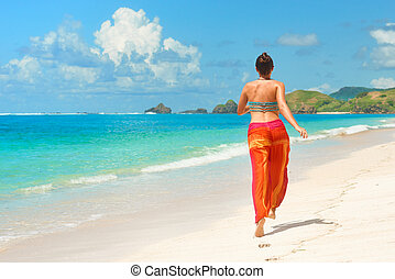 Happy woman in summer loose trousers running on tropical...