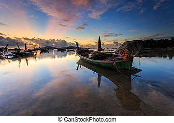 Traditional Thai longtail boat at sunrise beach in Phuket,...