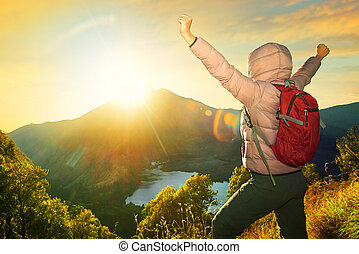 happy traveler with backpack standing on a rock with raised...
