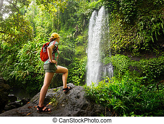 young woman backpacker looking at the waterfall in jungles....