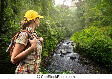 Woman hiker with backpack standing and enjoying rain forest...