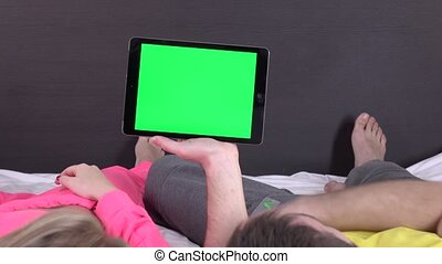 Sweet couple on bed watching something on white tablet gadget, green screen