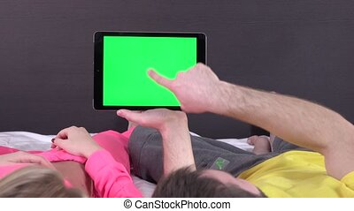 Sweet couple on bed watching something on white tablet...