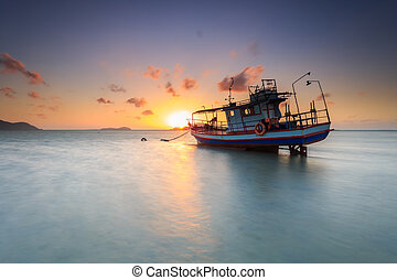 Fishing boat stand at sunrise beach in Phuket, Thailand