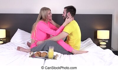 Couple having breakfast in their bed at home, croissants and...