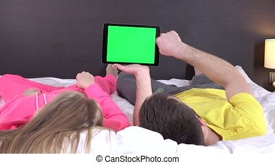 Young couple at bed watching something on tablet gadget,...