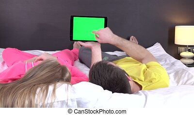 Young sweet couple at bed watching something on tablet...