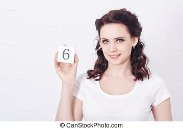 Girl in white t-shirt holding number six.