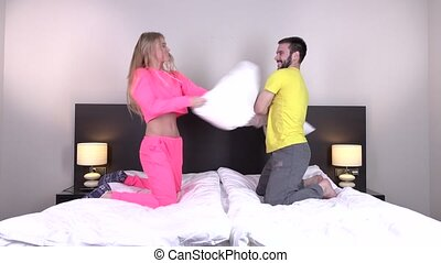 Portrait of sexy young couple having pillow fight in...